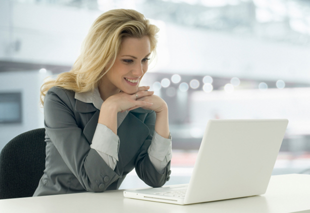 Image of smiling woman looking at laptop.